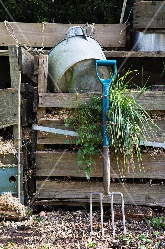 Gardening tools by a compost heap in a garden