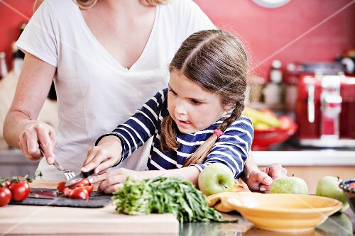 A mother and daughter chopping vegetables