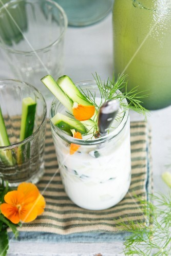 A yogurt dip with cucumber sticks and apple
