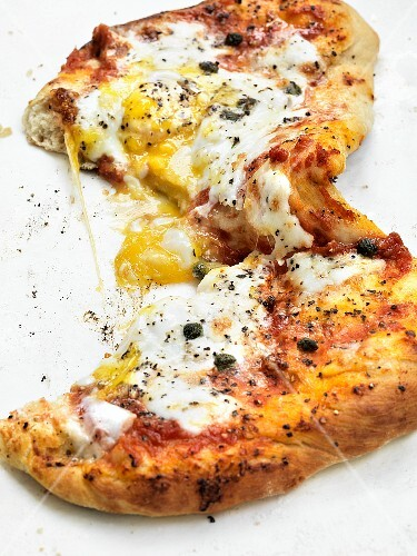 A pizza topped with egg and capers