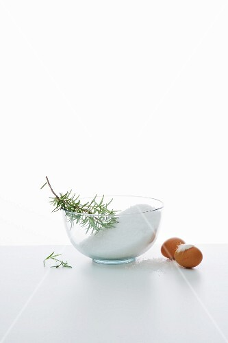 An arrangement of ingredients with salt, rosemary and eggs