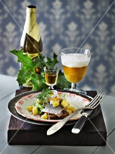 Soused herring on bread served with Aquavit and beer (Scandinavia)