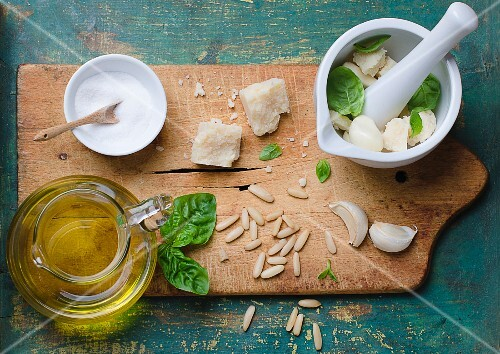 Ingredients for basil pesto on a chopping board