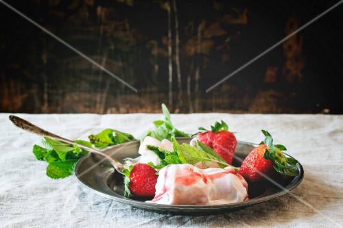 Strawberry ice cream with fresh mint and strawberries on a vintage plate