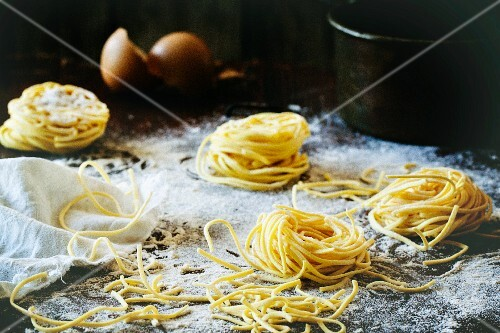 Homemade pasta on a wooden table with flour