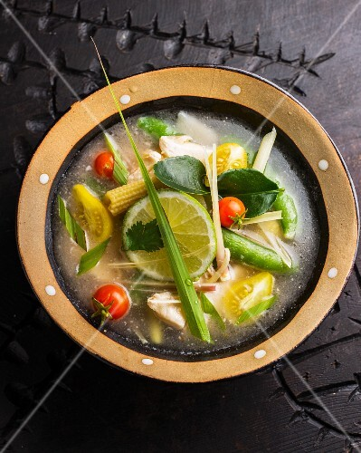 Soup with chicken, tomatoes, baby corn cobs and kaffir lime leaves