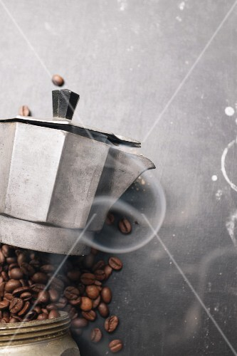 Steaming coffee and coffee beans with a vintage espresso maker