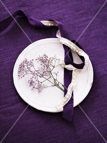 White plate on purple tablecloth decorated with purple flowers and satin and lace ribbons