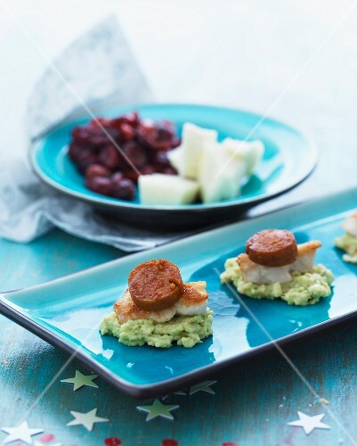 An appetiser comprising guacamole, roast pork and chorizo