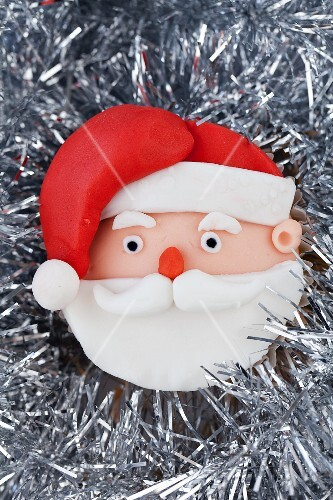 A Father Christmas cupcake on silver tinsel
