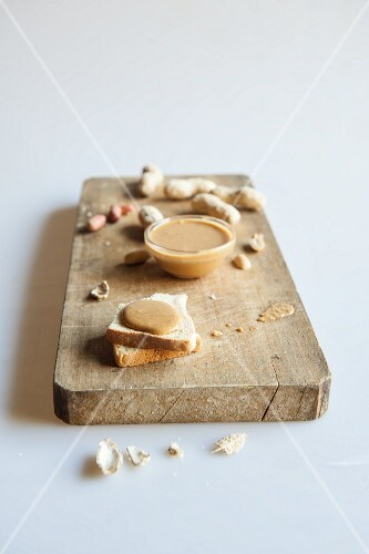 Toast topped with peanut butter and peanuts on a chopping board