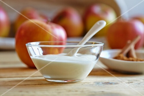 Natural yogurt in a glass bowl with fresh apples and cinnamon