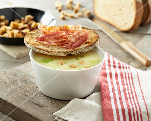 Potato soup with croutons and a slice of bread topped with bacon
