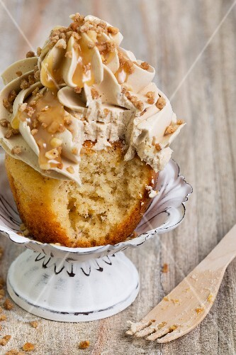 A cupcake topped with buttercream and caramel sauce with a bite taken out