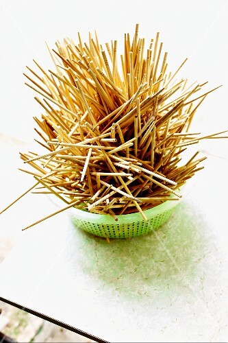Wooden toothpicks in a plastic sieve