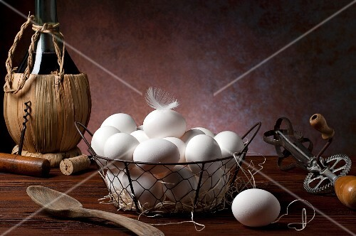 Fresh eggs in a wire basket next to antique kitchen utensils and a bottle of wine