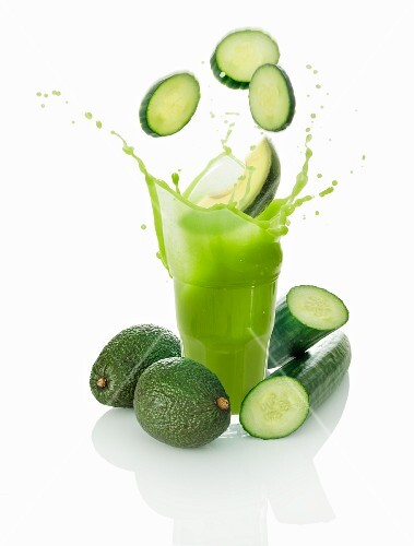Cucumber slices falling into a vegetables smoothie