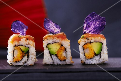 Three sushi rolls with salmon, avocado and purple potato crisps