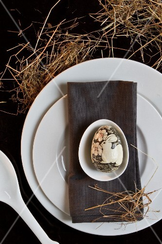 And Easter Place setting with a grey napkin and an artistically painted egg
