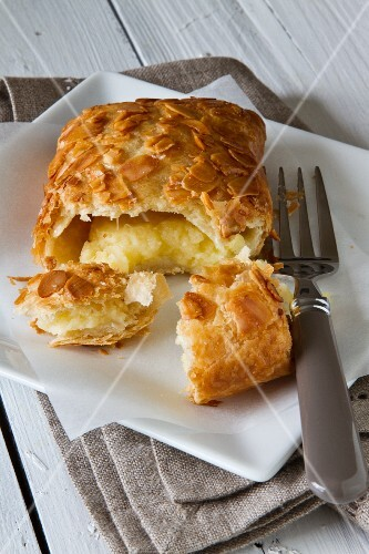 An apple turnover with a bite taken out of it on a plate with a cake fork