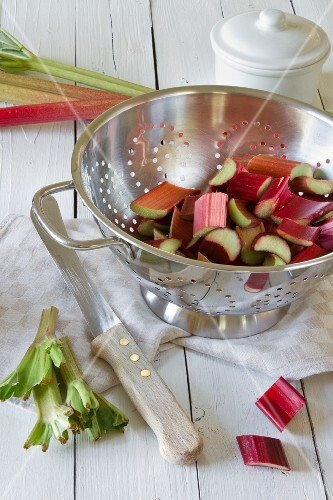 Sliced rhubarb in a silver colander on a wooden table
