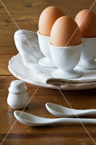 Three brown eggs in white porcelain egg cups