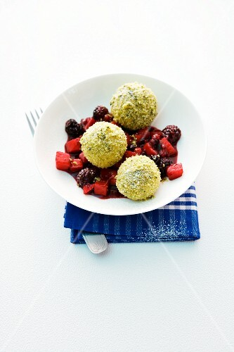 Sweet potato dumplings with pistachio crumbs on an apple and berry compote