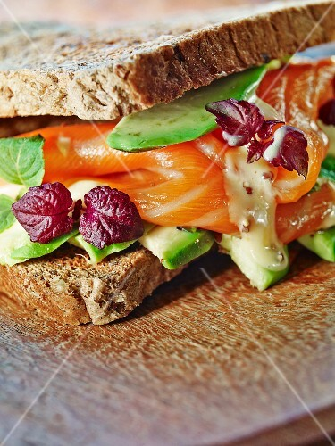 A salmon sandwich with avocado and basil