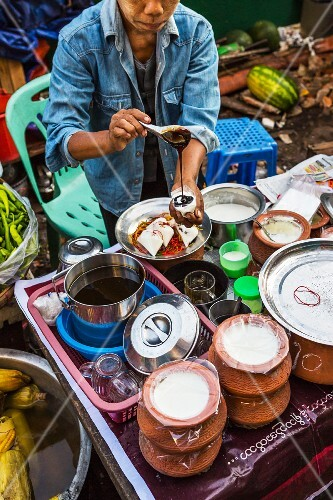 A Burmese woman drizzling syrup over yogurt at a market in Myanmar