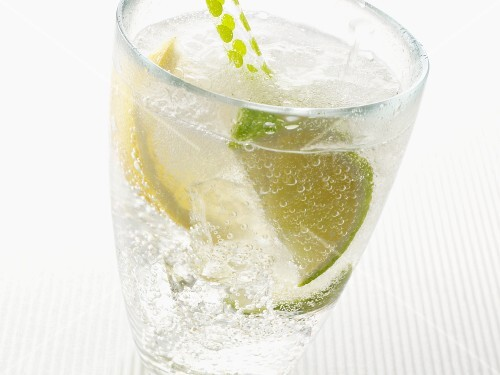 Sparkling mineral water with ice cubes and a lemon and lime wedge