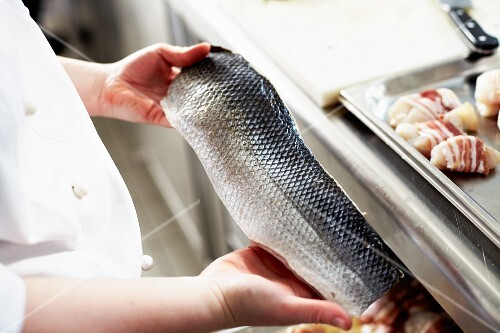 A chef holding a raw fish fillet