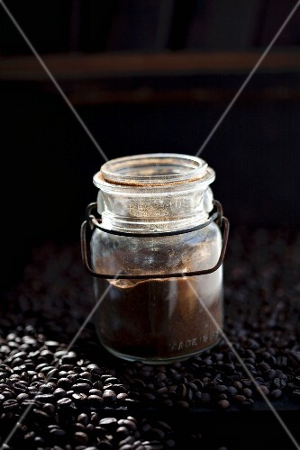 A jar of coffee powder on coffee beans