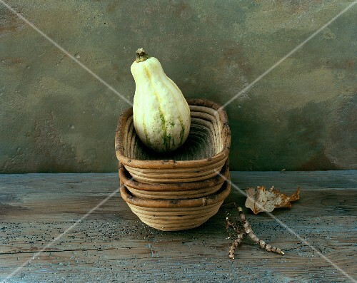 A green squash in a woven dish