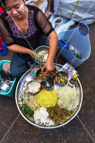 A woman selling noodles at a market in Myanmar
