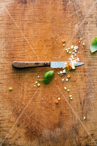 A vegetable knife and diced vegetables on a wooden surface