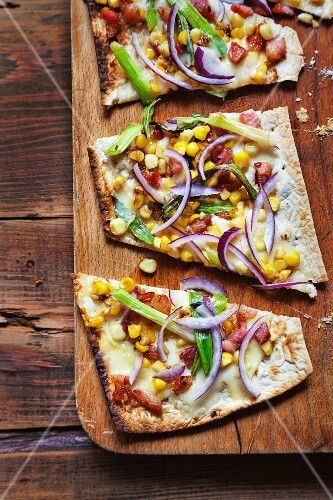 Unleavened bread with red onions, spring onions, sweetcorn, bacon and fontina cheese