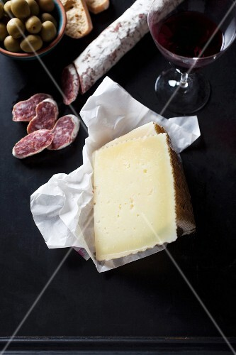 An arrangement of cheese, salami, olives and red wine