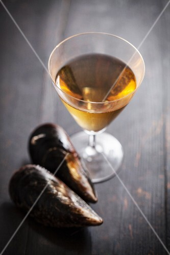 A glass of white wine and two mussels on a wooden surface