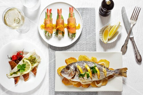 Three different fish dishes with lemons and white wine