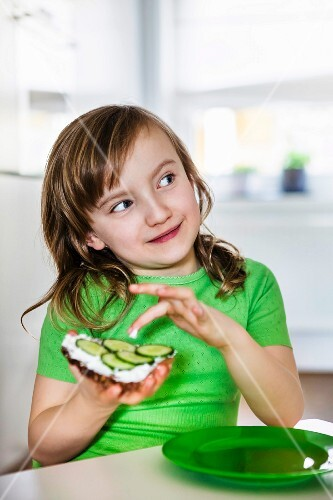 A girl in a green t-shirt eating a slice of bread topped with cream cheese and cucumber