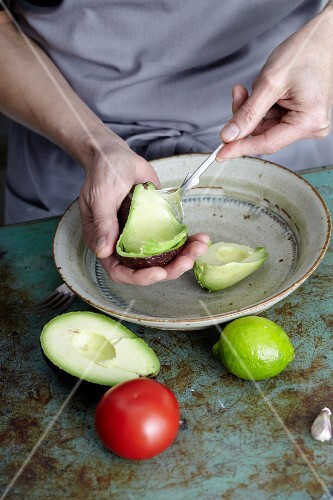 Guacamole being made: flesh being removed from an avocado