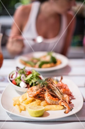 Prawns with lettuce and ships in a garden restaurant