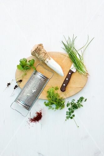 Horseradish root, a grater and herbs on and next to wooden board