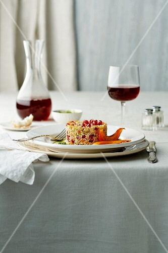 Couscous with pomegranate seeds, nuts and pumpkin wedges