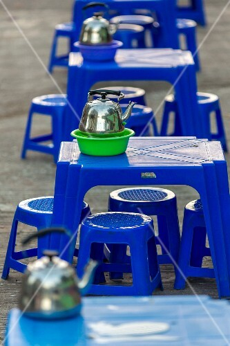 Plastic tables and stools with shiny teapots