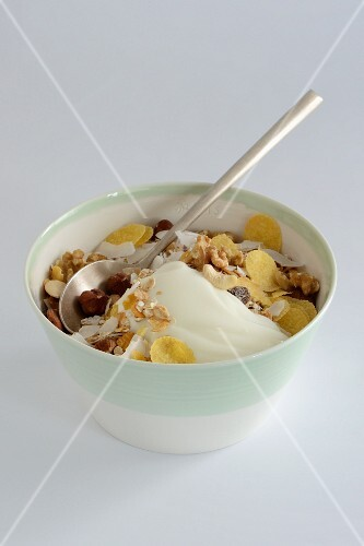 A bowl of muesli with yogurt against a white background