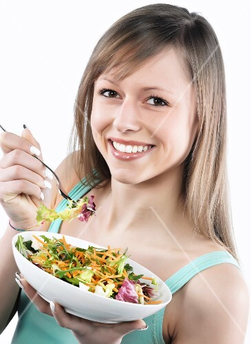 A sporty young woman eating a mixed leaf salad