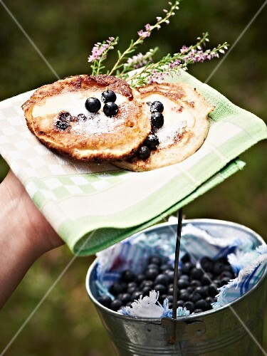 A hand holding pancakes with sugar and blueberries on a napkin