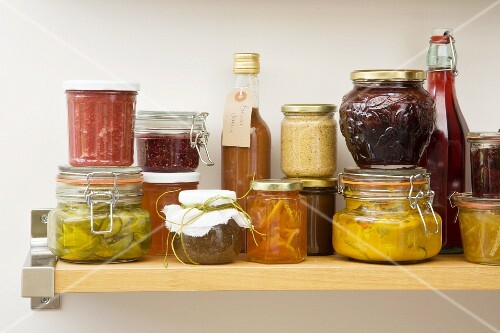 Jars and bottles of preserves and pickles on a wooden shelf