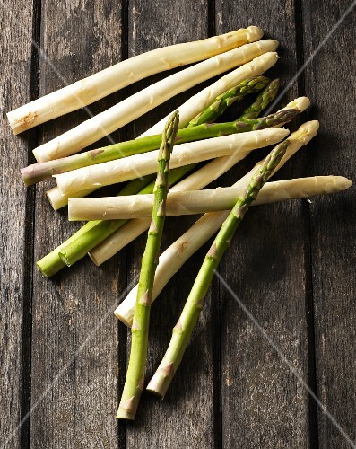 Green and white asparagus on a wooden table